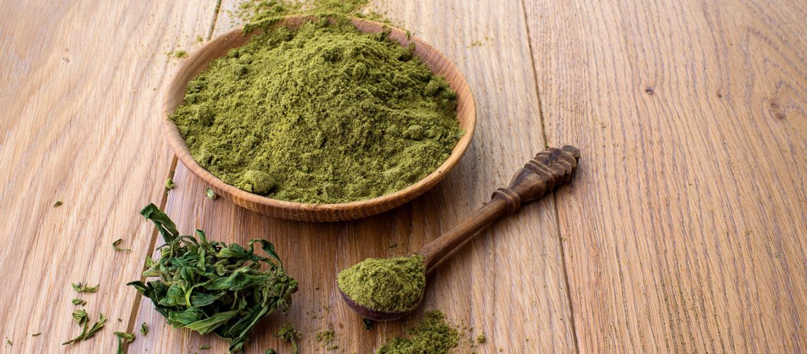 Hemp flour in wooden bowl, powder in spoon, on the table cannabis leaves on the background of the wooden boards